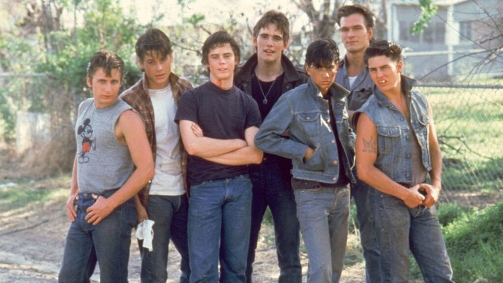 The cast playing The Greasers in THE OUTSIDERS: Emilio Estevez, Rob Lowe, C. Thomas Howell, Matt Dillon, Ralph Macchio, Patrick Swayze, and Tom Cruise.